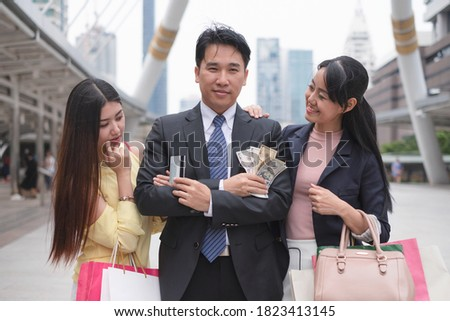 Asian businessman confident and flirting holding credit card and dollar cash standing between beautiful young asian women in urban #1823413145