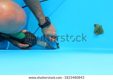 A worker welds plastic cover for water pool. Water pool cover replacement. Plastic Welding Machine. Swimming pool care concept. #1823480843