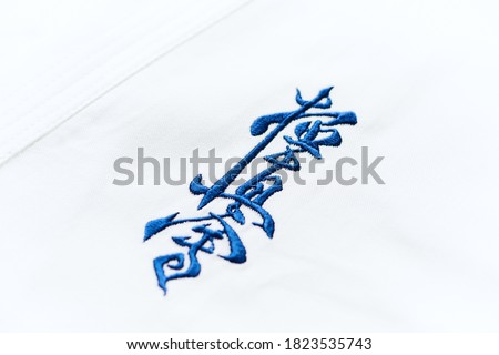 """Kyokushinkai karate symbol on cotton background. """"Kyokushin"""" is a style of stand-up, full contact karate and is Japanese for """"the ultimate truth"""". Royalty-Free Stock Photo #1823535743"""