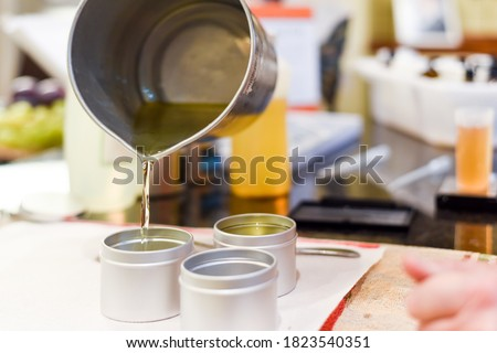 Creative occupation of candle making showing the pouring of liquid wax into jars Royalty-Free Stock Photo #1823540351