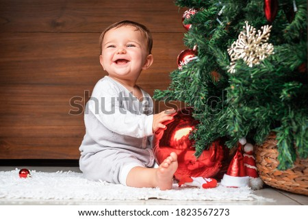 cute child with christmas tree.  happy baby sitting near a fir tree and holding a christmas ornament and smiling #1823567273