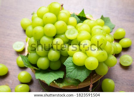 Green grape in Bamboo basket on wooden table in garden, Shine Muscat Grape with leaves in wooden background Royalty-Free Stock Photo #1823591504