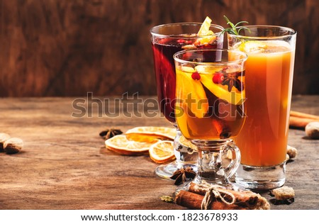 Selection of autumn or winter seasonal alcoholic hot cocktails - mulled wine, glogg, grog, eggnog, warm ginger ale, hot buttered rum, punch, mulled apple cider on wood background, copy space Royalty-Free Stock Photo #1823678933