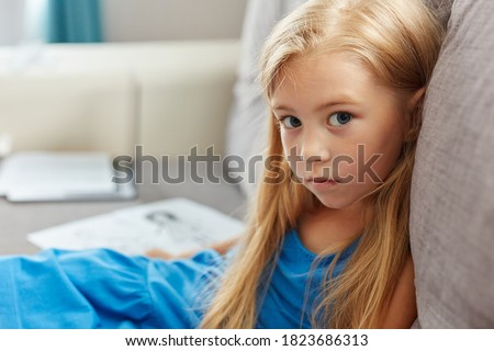 portrait of caucasian child girl in dress sitting on sofa in living , beautiful kid girl is sad. mom and dad drawing in the background as a symbol of divorce close up sad portrait
