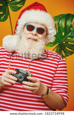 Joyful Santa Claus is relaxing and taking pictures in hot tropical countries. Christmas Holidays, tourist trips to the sea. Bright yellow background.