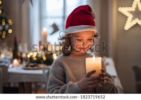 Happy small girl standing indoors at Christmas, holding candle. Royalty-Free Stock Photo #1823719652