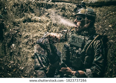 Smiling US army soldier, SEALs fighter, modern combatant in combat uniform, plate carrier, ballistic glasses and battle helmet resting after fight, sitting in trench at night and smoking cigarette Royalty-Free Stock Photo #1823737286