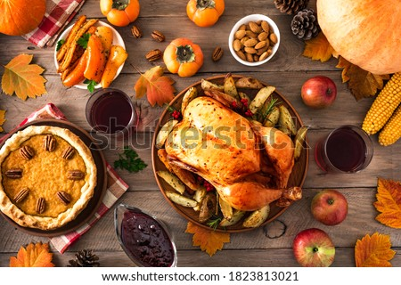 Thanksgiving dinner with chicken, cranberry sauce, pumpkin pie, wine, seasonal vegetables and fruits on wooden table, top view. Traditional autumn holiday food concept.