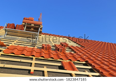 Roofing work, new covering of a tiled roof Royalty-Free Stock Photo #1823847185