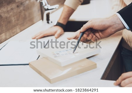 Close up manager in suit is showing different materials and color swatches to couple clients in kitchen store.The seller shows the strength of materials for buyers.  Royalty-Free Stock Photo #1823864291
