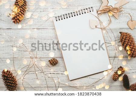 Blank notepad page surrounded by pine cones and New Year's decor on a white wooden background copy space. Christmas wishlist Royalty-Free Stock Photo #1823870438