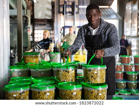 Afro-american male worker stocks plastic containers and cans with olives in warehouse. High quality photo