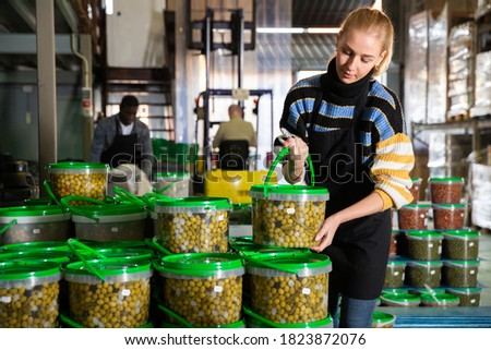 Female worker stocks plastic containers and cans with olives in warehouse. High quality photo