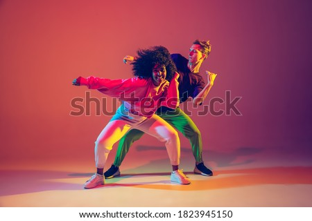 Stylish man and woman dancing hip-hop in bright clothes on green background at dance hall in neon light. Youth culture, hip-hop, movement, style and fashion, action. Fashionable portrait. Royalty-Free Stock Photo #1823945150