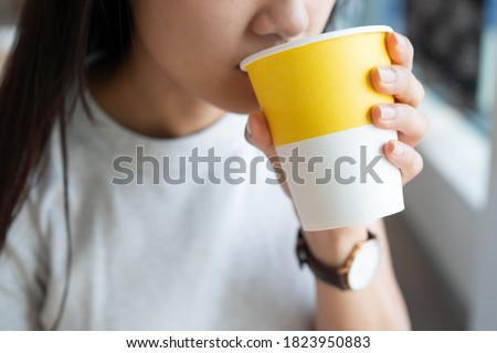 Close up of the Asian lady holding the hot drink paper cup with one hand and sipping the hot beverage Royalty-Free Stock Photo #1823950883