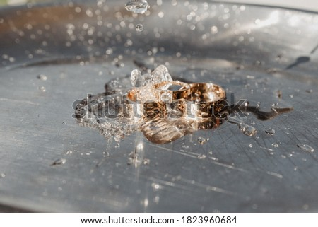 wedding rings on a chrome plated surface. water drops with reflections of light. water splashes