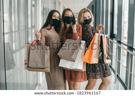 Young beautiful women in dresses, black medical masks and bags walk in the mall, shopping during the quarantine. Life after pandemic, fun, joy, friends, clothes, goods, gifts business. #1823961167