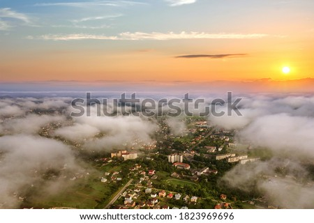 Sunset over rural area in town with clouds and yellow sun. Royalty-Free Stock Photo #1823969696