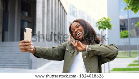 Beautiful young African American woman posing and smiling to smartphone camera while taking selfie photo at street.
