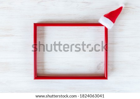 Red frame with small Santa Claus hat on white vintage wooden background. Minimalist Christmas decoration with copy space. Mockup for festive time. Christmas, New Year, winter concept.