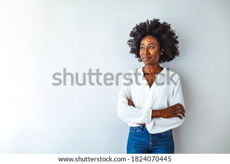 Close up attractive young black woman. Photo of young curly girl. Studio shot of a young businesswoman against a gray background. Portrait of young woman looking to camera with arms crossed Royalty-Free Stock Photo #1824070445