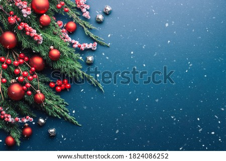 Christmas border with fir branches and red decorations on blue background with snow. Royalty-Free Stock Photo #1824086252