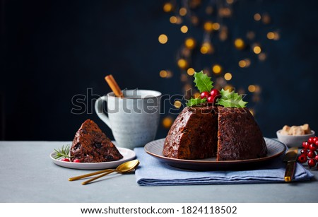 Christmas pudding, fruit cake with cup of tea. Traditional festive dessert. Dark background with lights garland. Copy space. #1824118502