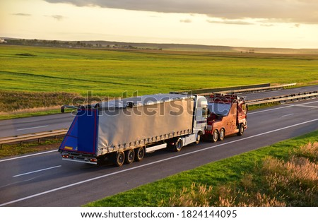 Heavy Recovery Truck Tows a Semitrailer truck on highway. Emergency Rescue Wrecker Tow Truck coach haul car along road. Towing Vehicle during work. Сar accident on the freeway Royalty-Free Stock Photo #1824144095