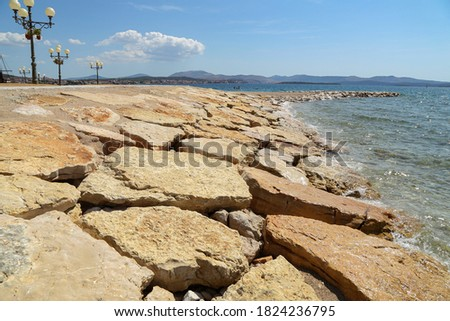 Sea embankment lined with large natural stones Royalty-Free Stock Photo #1824236795