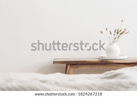 Modern white ceramic vase with dry Lagurus ovatus grass and marble tray on vintage wooden bench, table. Blurred beige linen blanket in front. Scandinavian interior. Empty white wall, copy space. Royalty-Free Stock Photo #1824267218