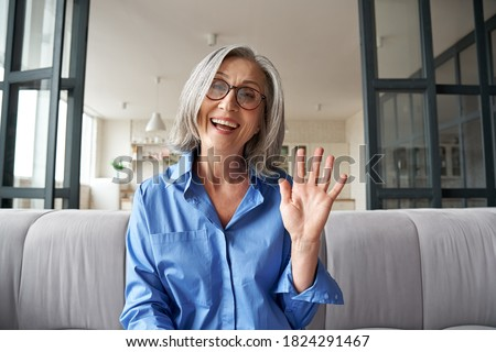 Happy mature middle aged woman online teacher waving hand talking to web cam video conference calling in virtual webcamera chat meeting by distance remote vidoecall. Headshot portrait. Webcam view. Royalty-Free Stock Photo #1824291467
