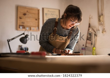 A young female carpenter working as wood designer in a small carpentry workshop. Young business woman handcrafting a piece of timber and designing new house furniture. Entrepreneurs concept lifestyle #1824322379