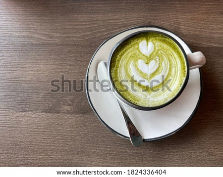 Hot Green Tea Latte has a beautiful milk bubble pattern on a brown wooden table. Top view of hot ceramic green tea cup in the morning coffee shop. Milk foam art.