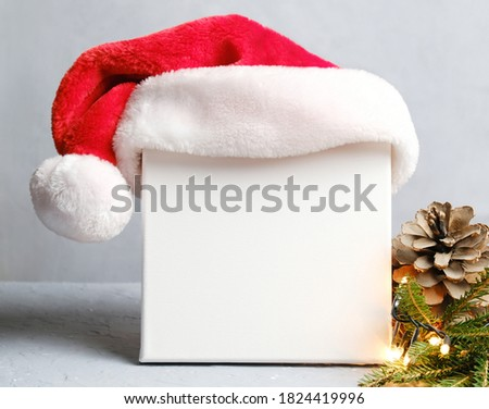 Blank square canvas board with Santa hat. Mockup poster, Christmas concept.