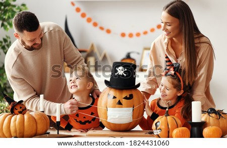Cheerful family   makes jack o lantern  in medical masks out of a pumpkin and  decorates house  in cozy kitchen during Halloween celebration at home during the covid19 coronavirus pandemic #1824431060