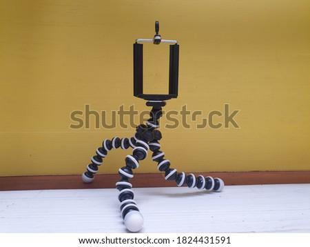 Flexible octopus tripod on yellow background.selective focus