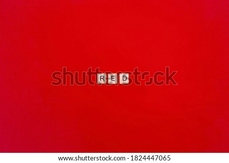 The word red. Wooden blocks with an inscription on top on a red background. Color scheme concept.