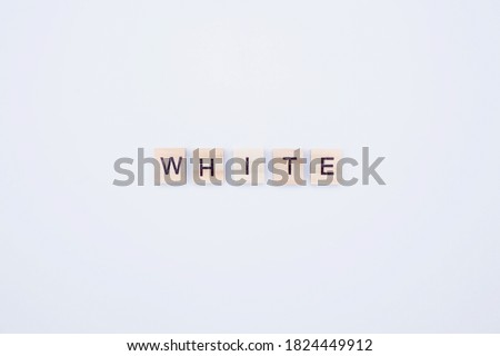 "The word ""white"". Wooden blocks with an inscription on top on a white background. The concept of color schemes."
