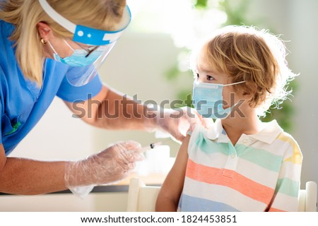 Coronavirus vaccination. Covid-19 vaccine. Doctor vaccinating child. Kids at clinic. Little boy getting flu shot. Pediatrician examining kid and giving injection. Virus prevention. Health care. #1824453851