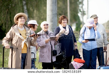 A group of positive senior elderly people travelers using tablets waiting for train before going on a trip