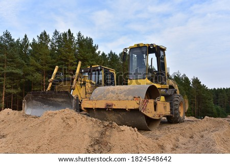 Dozer and Vibro Roller Soil Compactor at road construction and bridge projects in forest area. Heavy machinery for road work. Building a road works.  #1824548642