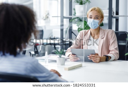 New normal and modern interview during covid-19 outbreak. HR manager with tablet looking for employee, watch at african american woman through protective glass in modern office interior, free space Royalty-Free Stock Photo #1824553331