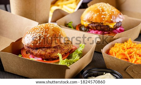 Street food. Meat cutlet burgers are in paper boxes. Food delivery. Royalty-Free Stock Photo #1824570860