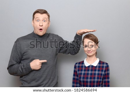 Studio shot of surprised tall man showing height of short woman, pointing at her with finger, both are standing over gray background. Concept of diversity of people's heights, tall and short persons Royalty-Free Stock Photo #1824586694