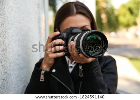 Private detective with camera spying near building on city street Royalty-Free Stock Photo #1824591140