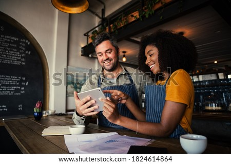 Manager and waitress laughing at designs on digital tablet standing with hot coffee in cafe  Royalty-Free Stock Photo #1824614864