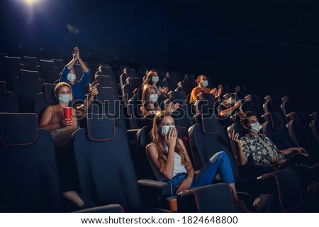 Cinema in quarantine. Coronavirus pandemic safety rules, social distance during movie watching. Men, women in protective face mask sitting in a rows of auditorium. Leisure time, youth culture concept. Royalty-Free Stock Photo #1824648800