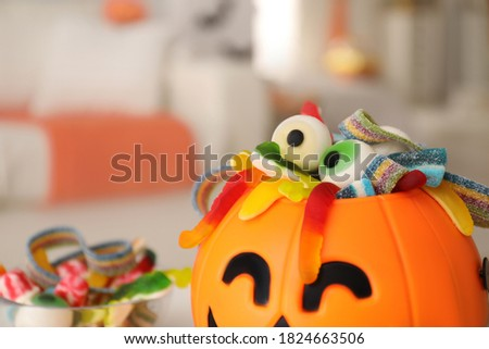 Halloween trick or treat bucket with different sweets indoors, closeup