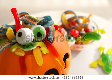 Halloween trick or treat bucket and many different sweets on white table, closeup
