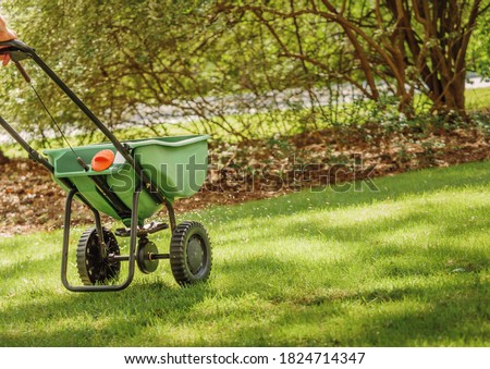 Fertilizing and seeding residential backyard lawn with manual grass fertilizer spreader. Royalty-Free Stock Photo #1824714347